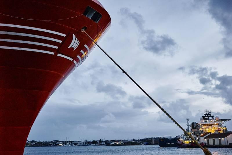 I forgrunnen ser vi baugen til et skip, i bakgrunnen ligger et annet skip til kais. Foto: Øivind Haug