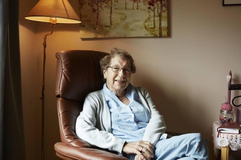 En eldre kvinne sitter i godstolen sin og smiler til kamera. Foto: Øivind Haug
