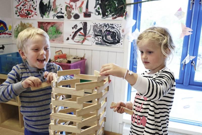 To barnehagebarn bygger et høyt tårn og stråler av glede. Foto: Øivind Haug