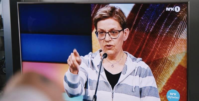 Dame på TV-skjerm som peker.