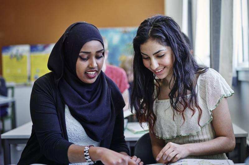 To smilende jenter på ungdomstrinnet gjør skolearbeid sammen. Foto: Øivind Haug