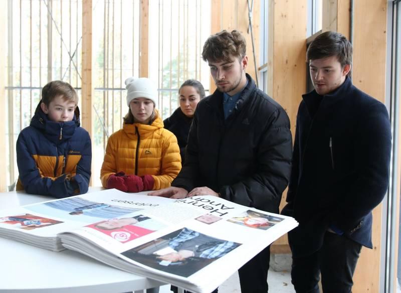 Fem barn og unge ser i en bok om 22. juli i Hegnhuset på utøya.