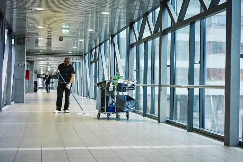 En renholdsarbeider står og vasker en gang. Foto: Øivind Haug