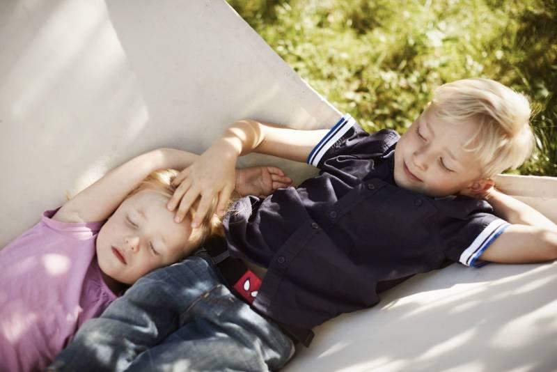 To barn ligger og slapper av i en hengekøye i sola. Foto: Øivind Haug
