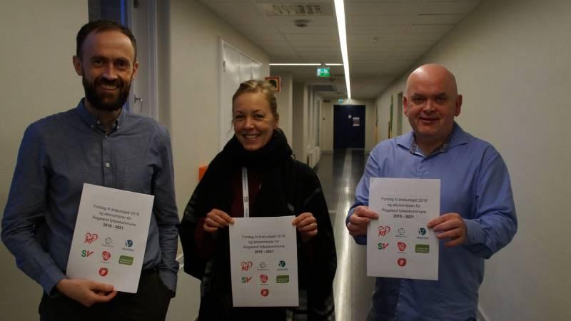 Fra venstre står Simon Næsse, Marianne Chesak og Jarle Nilsen. Alle holder et eksemplar av budsjettforslaget til flertallet.