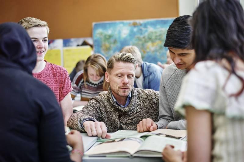 En gruppe elever sitter samlet rundt læreren som forklarer og veileder dem gjennom oppgaver. Foto: Øivind Haug