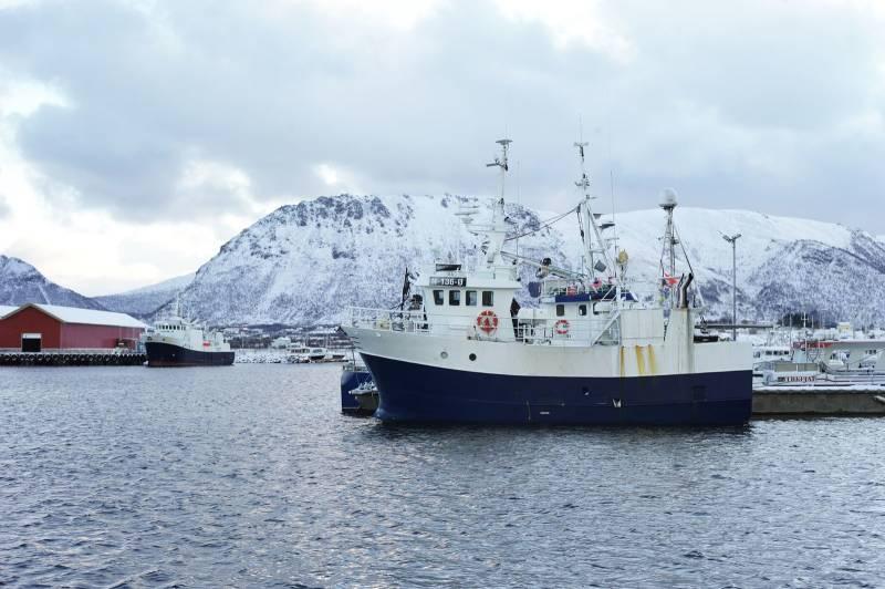En fisketråler ligger til kais i en fjord, snødekte fly i bakgrunnen. Foto: Øivind Haug