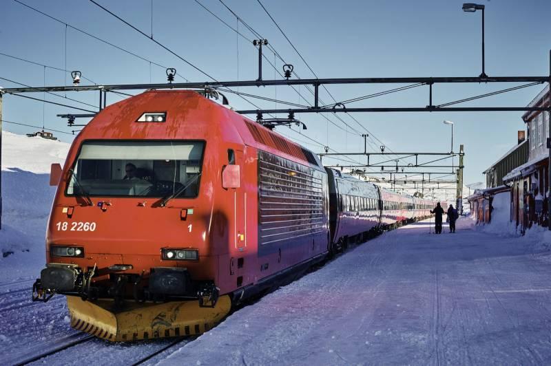 Et tog fra NSB har stoppet på en stasjon på fjellet, blå himmel og snøkledd landskap. Foto: Øivind Haug