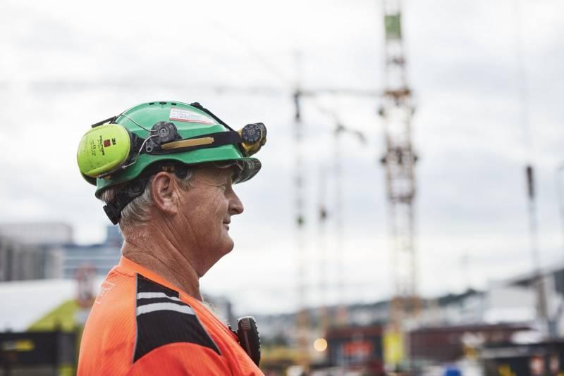 En anleggsarbeider står i profil, i bakgrunnen er det geisekraner. Foto: Øivind Haug