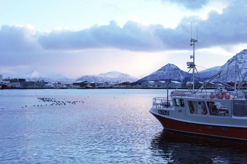 En båt ligger til kais, fjellene og havet rundt er lyst opp av et mildt, blårosa lys. Foto: Øivind Haug