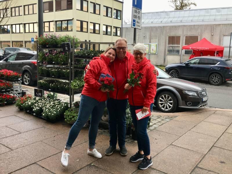 Jenny og to partikamerater deler ut roser og smiler