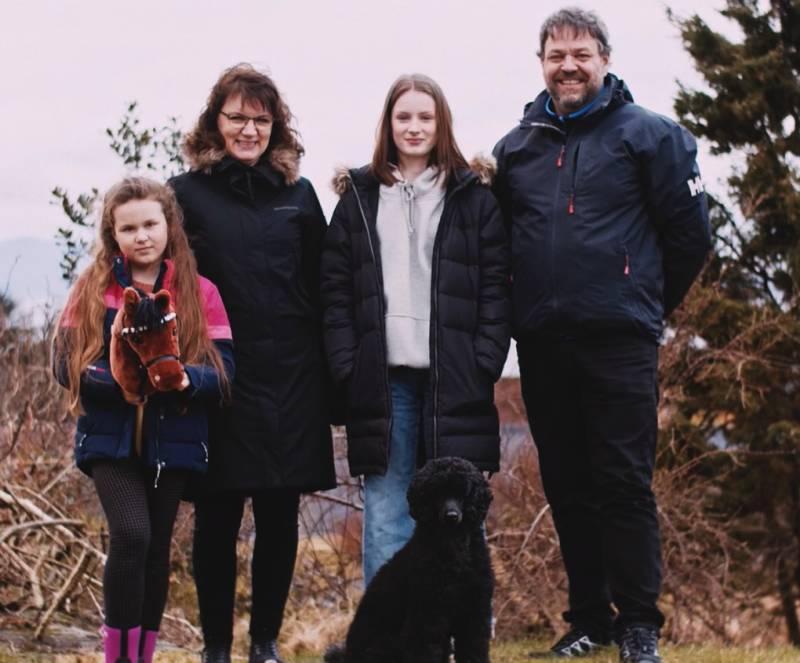 Familie på fire og en hund, utendørs.