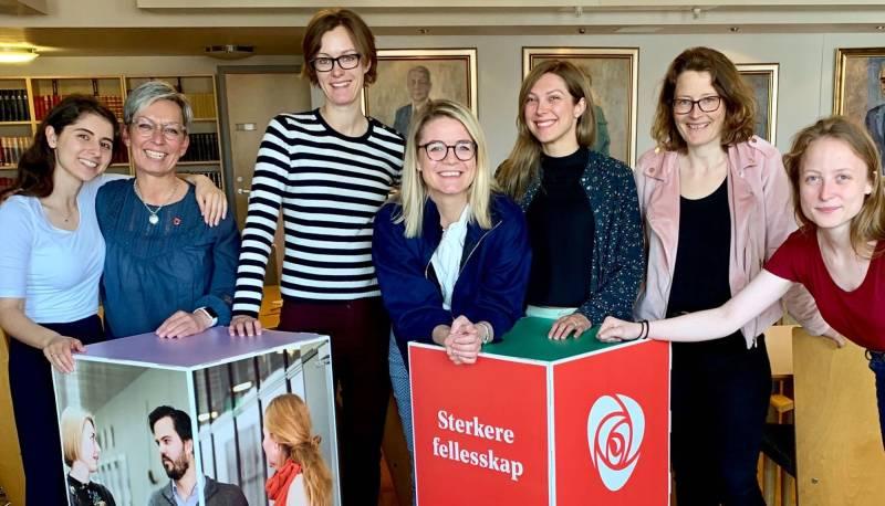 """Styringsgruppa i kvinnenettverket står foran en boks med bilder av forskjellige mennesker, og en rød boks med partirosen og teksten """"Sterkere fellesskap""""."""