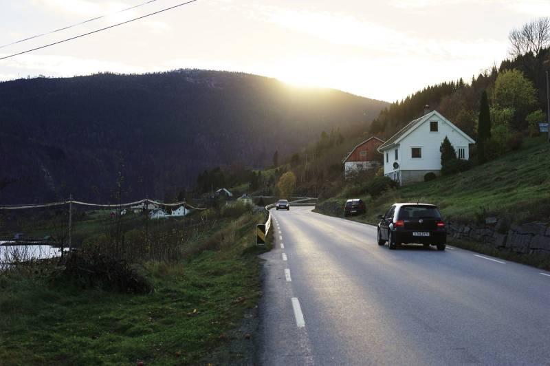 En landevei strekker seg gjennom landskapet, i bakgrunnen går sola ned bak et fjell. Foto: Øivind Haug