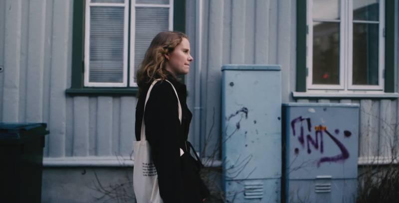 Jente som går bortover vei med handlenett på skulderen.
