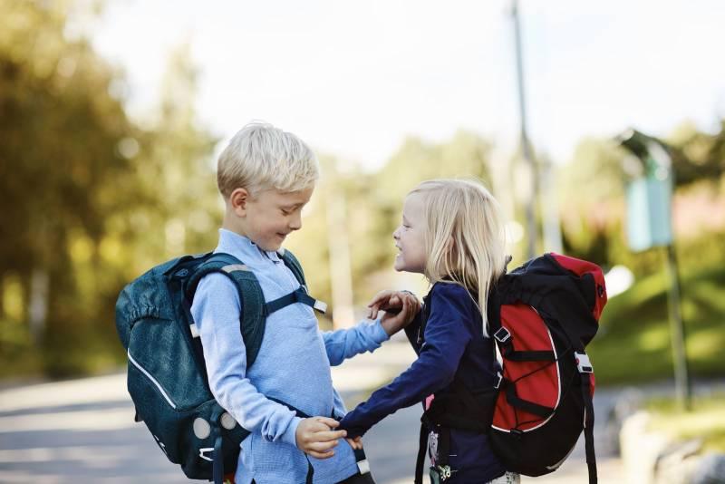 To skolebarn holder hender og smiler på vei til skolen. Foto: Øivind Haug