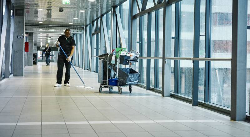 En mannlig renholdsarbeider vasker en korridor