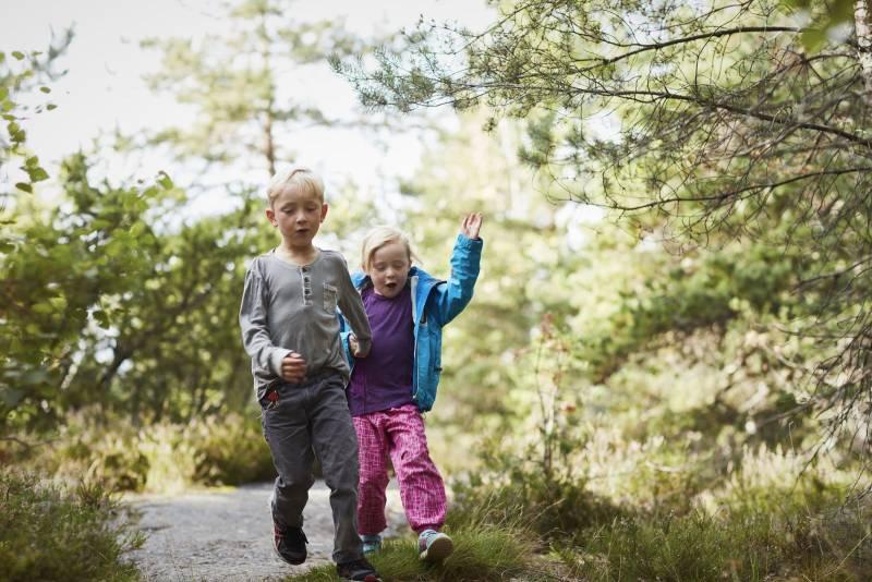 To barn går jublende på en skogssti. Foto: Øivind Haug