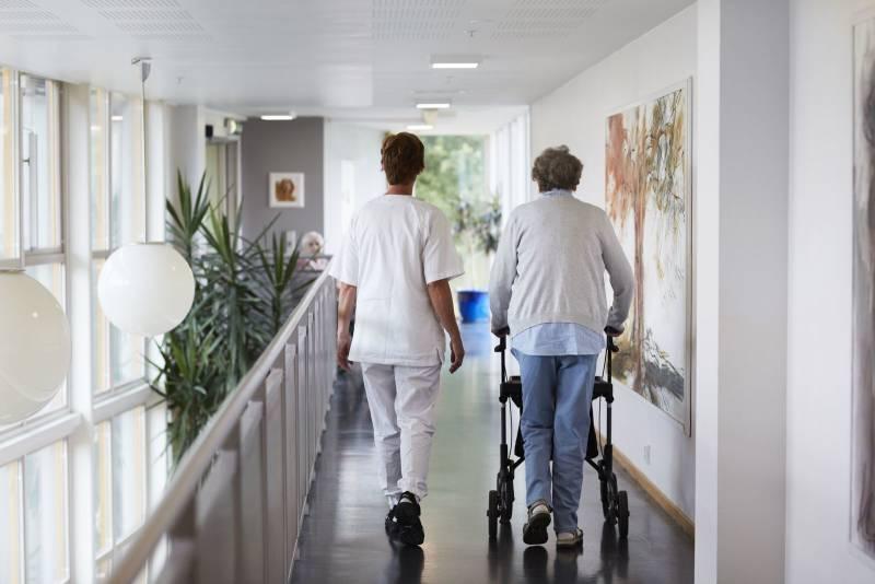 En eldre kvinne geleides gjennom gangene av et sykehjem av en sykepleier. Foto: Øivind Haug