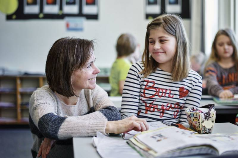 En lærer hjelper en av elevene sine med skoleoppgaver. Foto: Øivind Haug