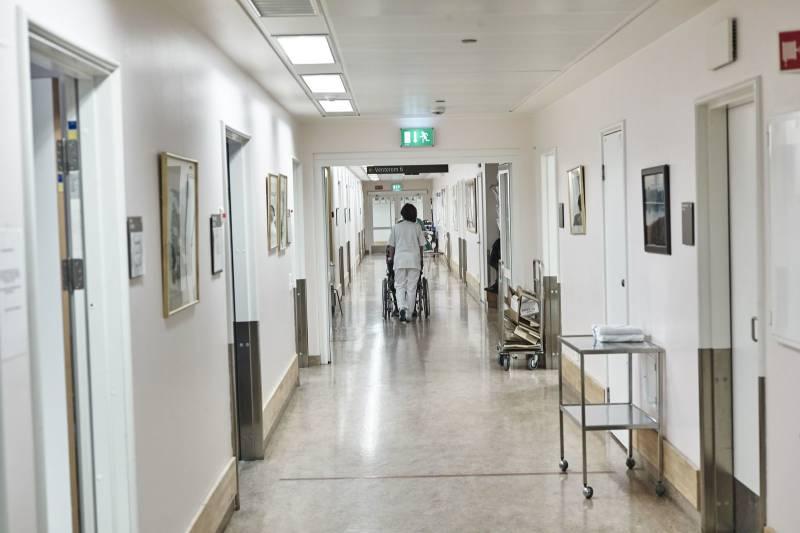 Bilde av en sykehusgang, i enden ruller en sykepleier en pasient. Foto: Øivind Haug