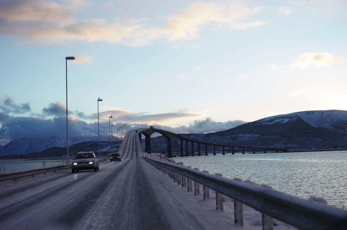 Bro i vinterlandskap med biler.
