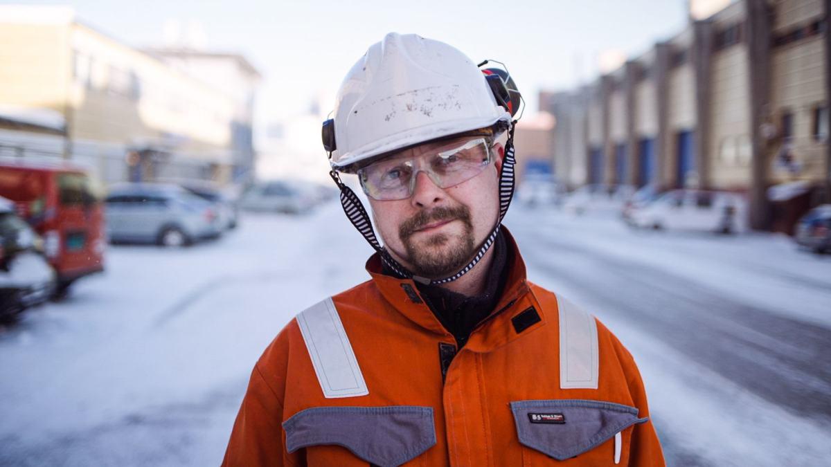 Mann med hjelm og orange kjeledress. Utendørs.