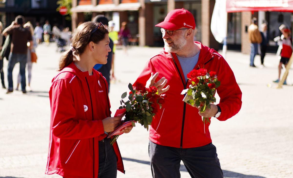 Valgkamp i Lillestrøm - yngre jente og eldre mann smiler med roser i hendene og valgkampjakker på.
