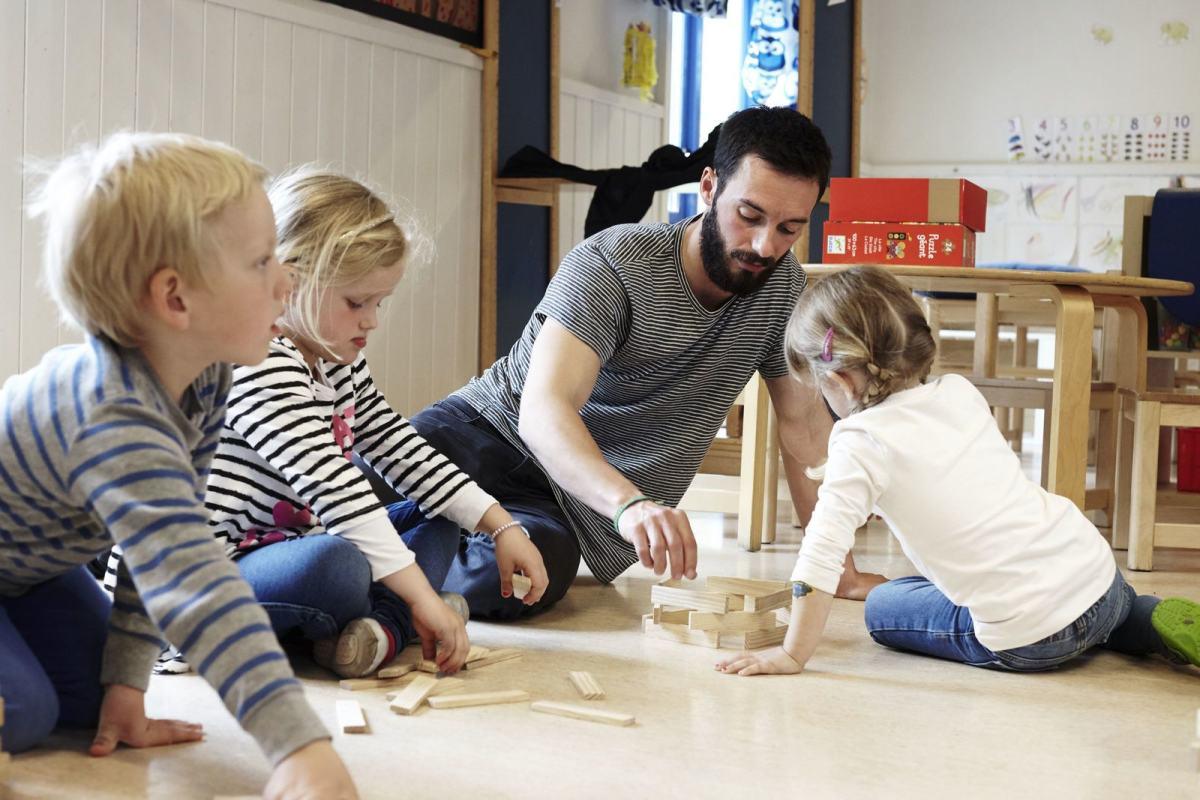 Tre barnehagebarn bygger kaplaklosser med en ansatt. Foto: Øivind Haug