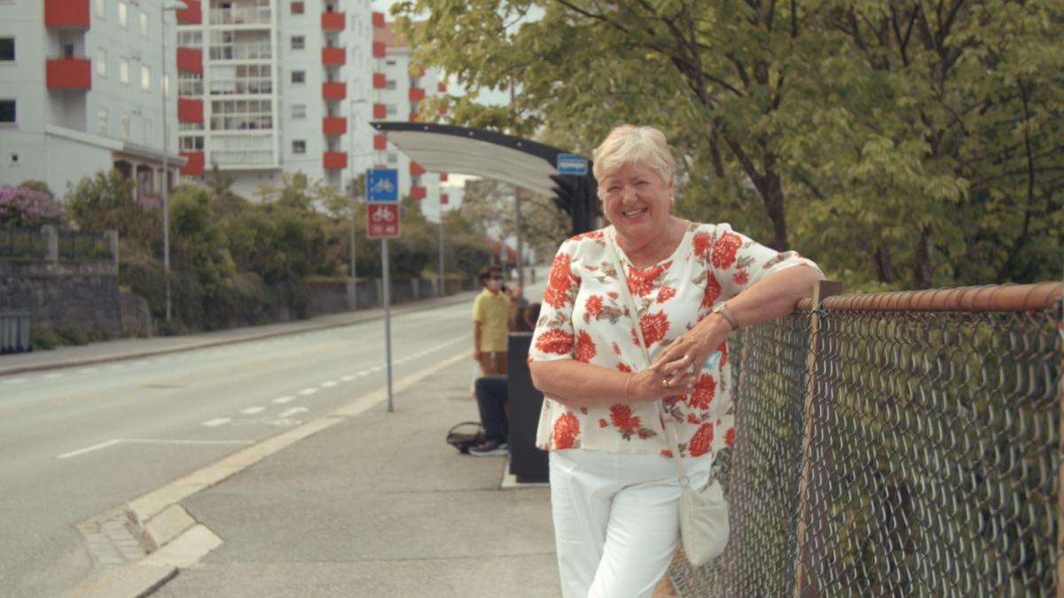 Eldre dame ved busskur.