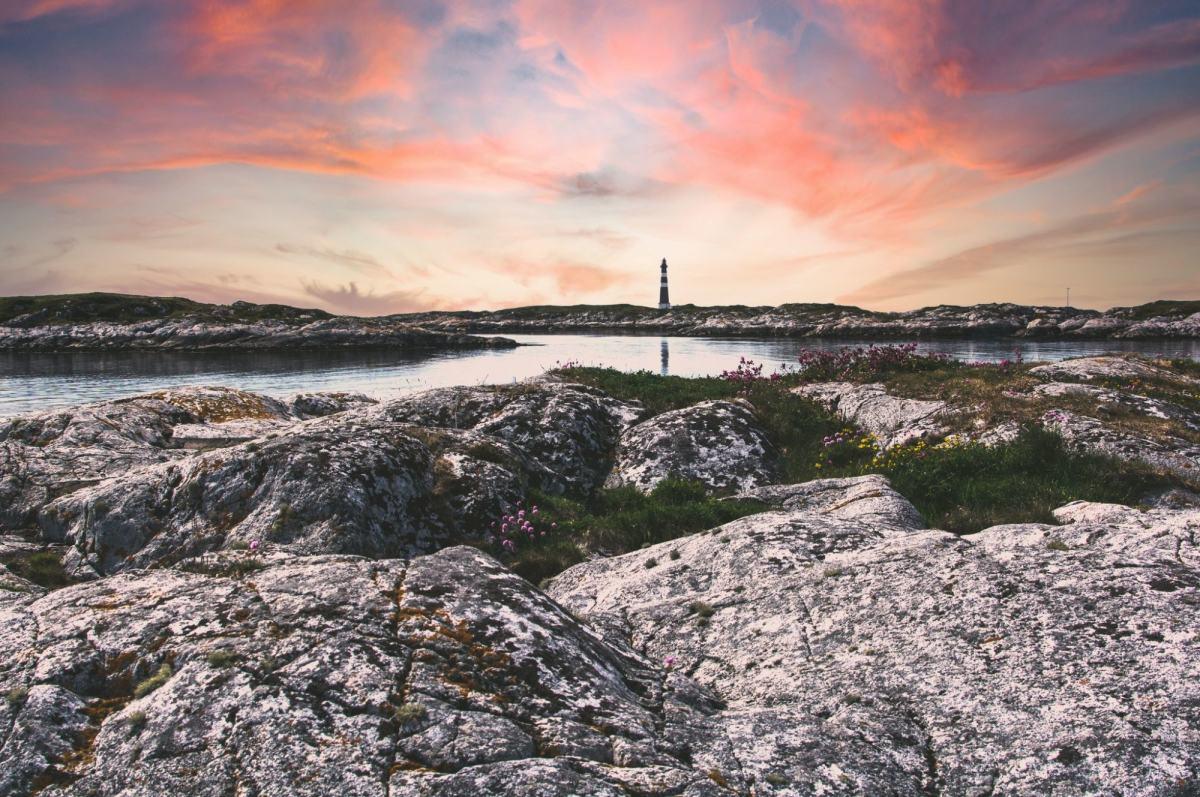 Landskap med stein, rødlig himmel og fyrtårn i bakgrunnen. Foto: Hasse Lossius (Unsplash)