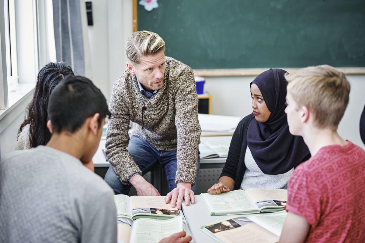 En gruppe ungdomsskole elever sitter samlet rundt læreren sin. Foto: Øivind Haug