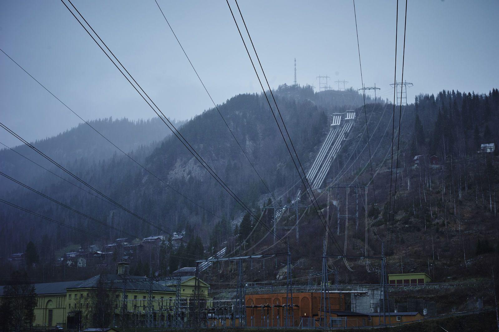 Lange kraftkabler strekker seg gjennom landskapet og opp en bakke. Foto: Øivind Haug