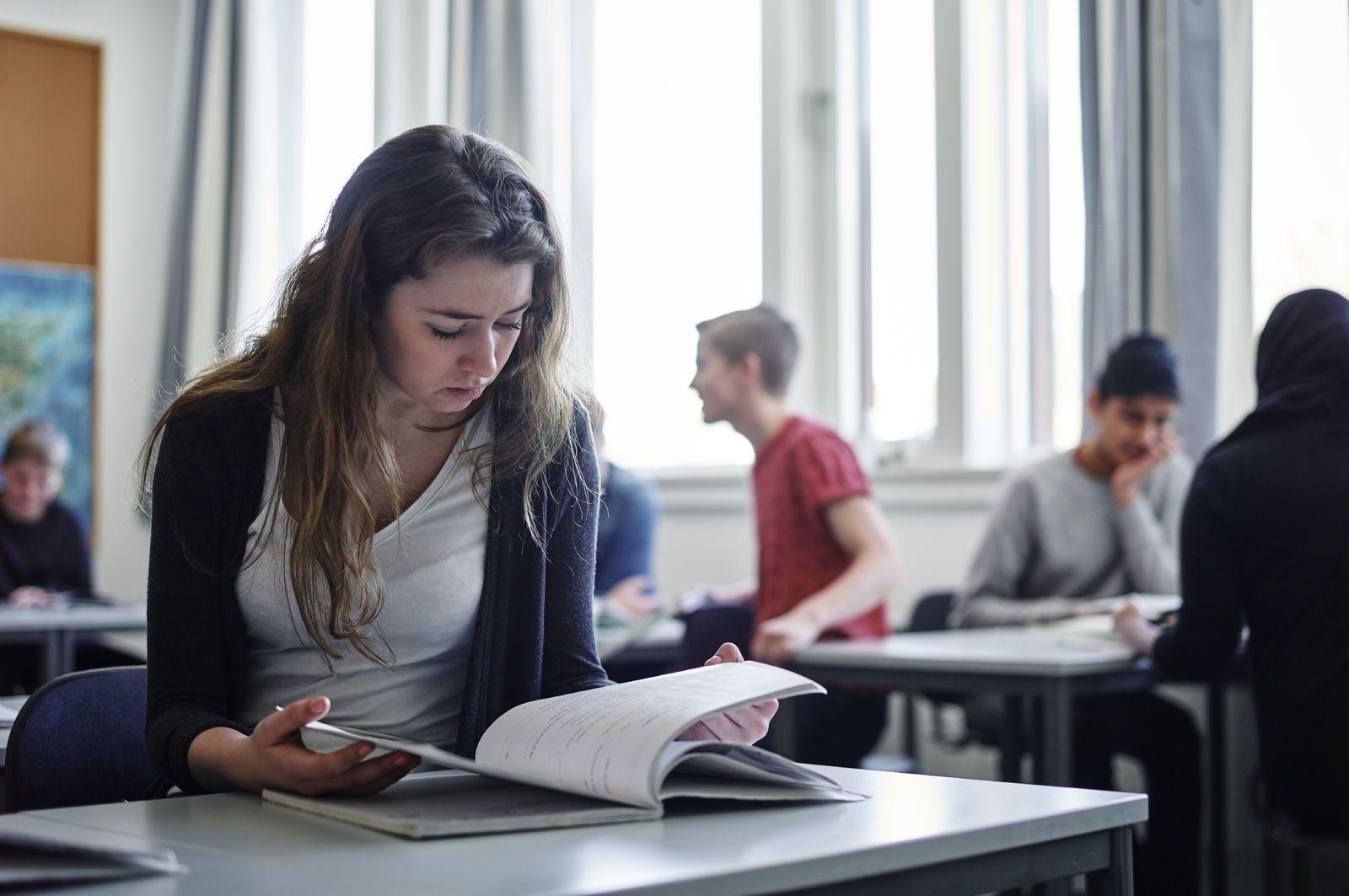 En elev sitter konsentrert ved pulten sin og leser. Foto: Øivind Haug
