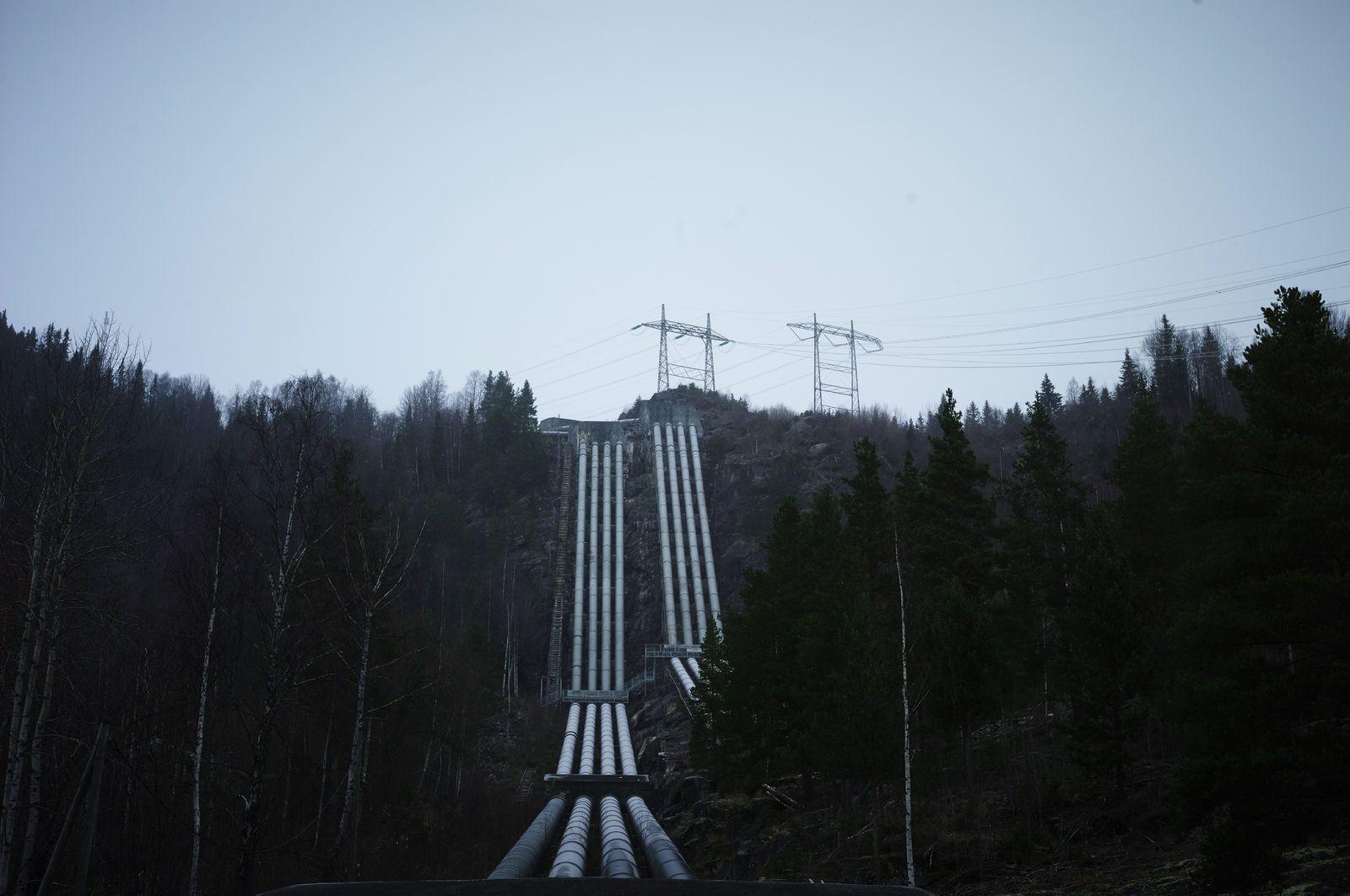 Brede kraftledninger strekker seg opp en fjellskrent. Foto: Øivind Haug