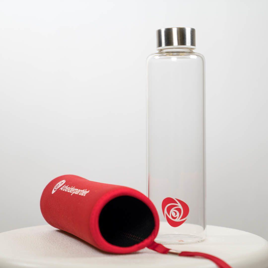 Glassflaske med skrukork av metall og Ap-logo og rødt futteral