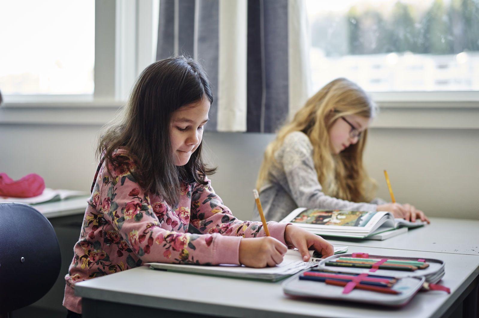 To barneskolejenter sitter og jobber på pultene sine. Foto: Øivind Haug