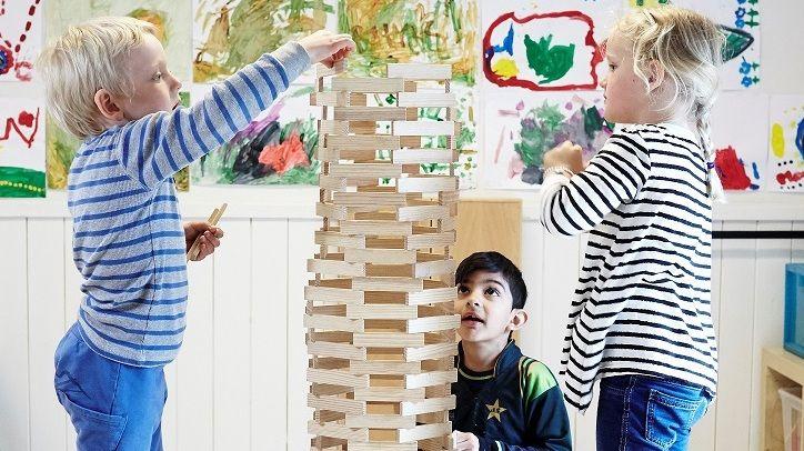 Tre barn bygger tårn av treklosser