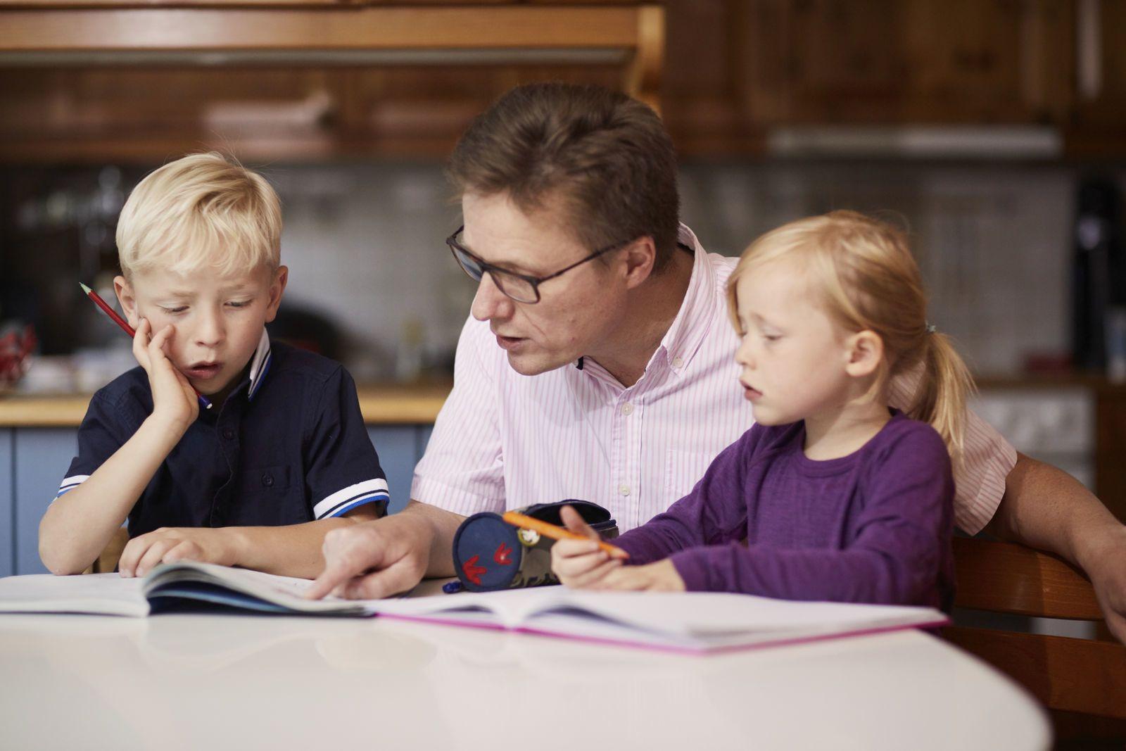 En far hjelper sine to barn med lekser hjemme på kjøkkenbordet. Foto: Øivind Haug