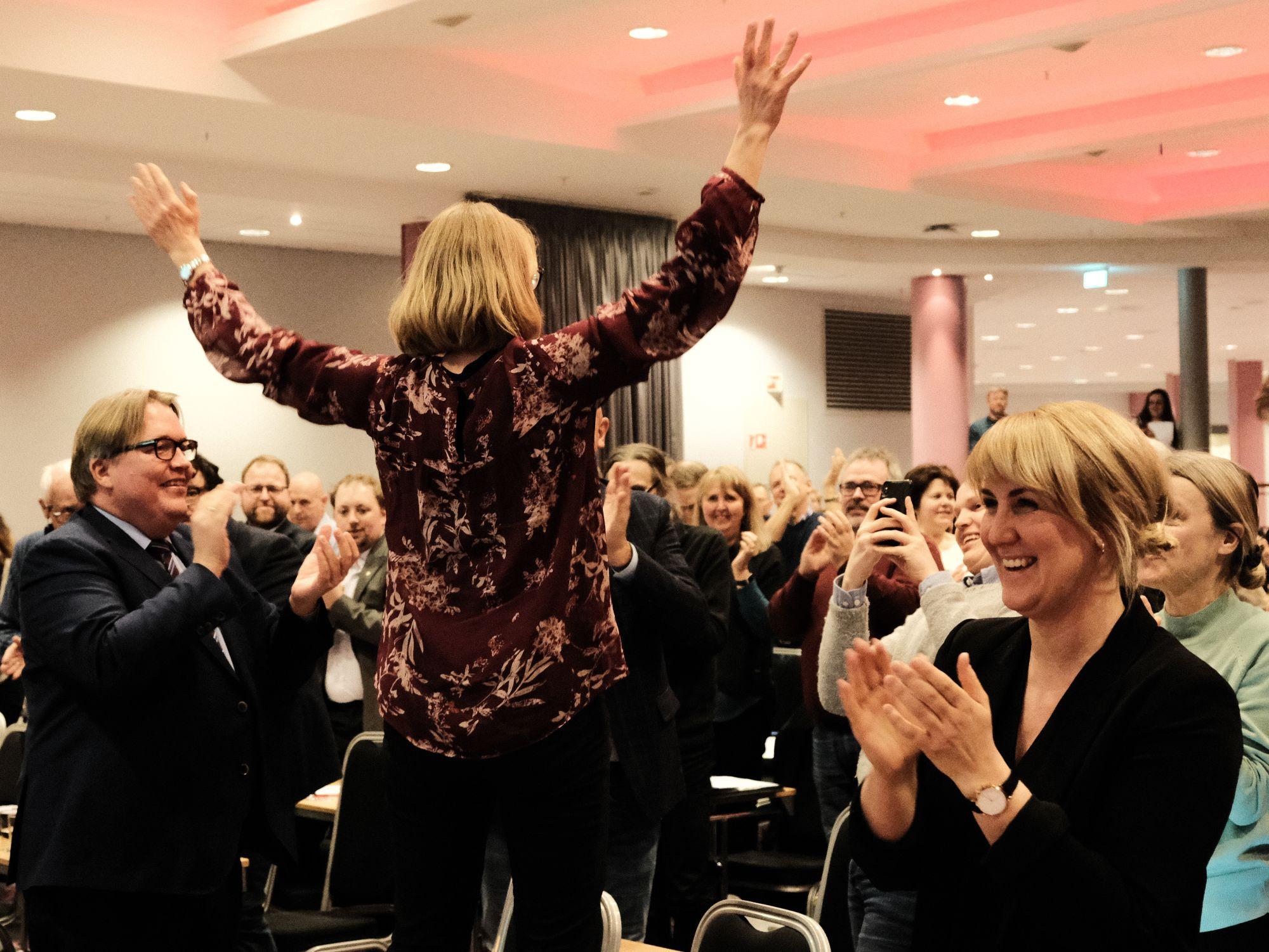 Anniken Huitfeldt står på en stol med armene i været. Årsmøtet klapper, hun er valgt som leder av Akershus Ap.