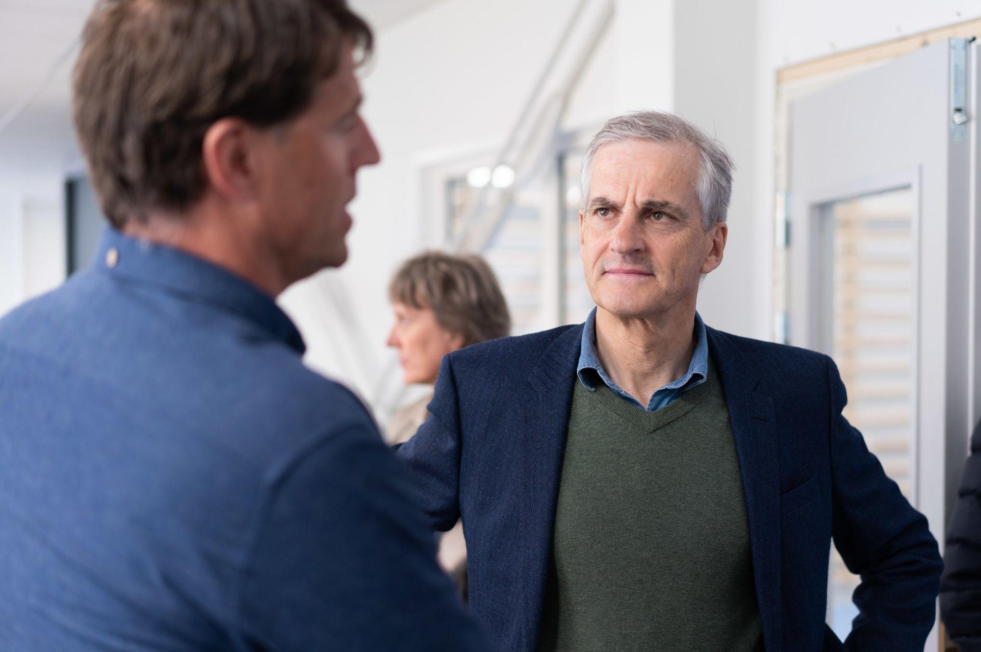 Jonas Gahr Støre ser alvorlig på mann som snakker i forgrunnen av bildet med ryggen til.