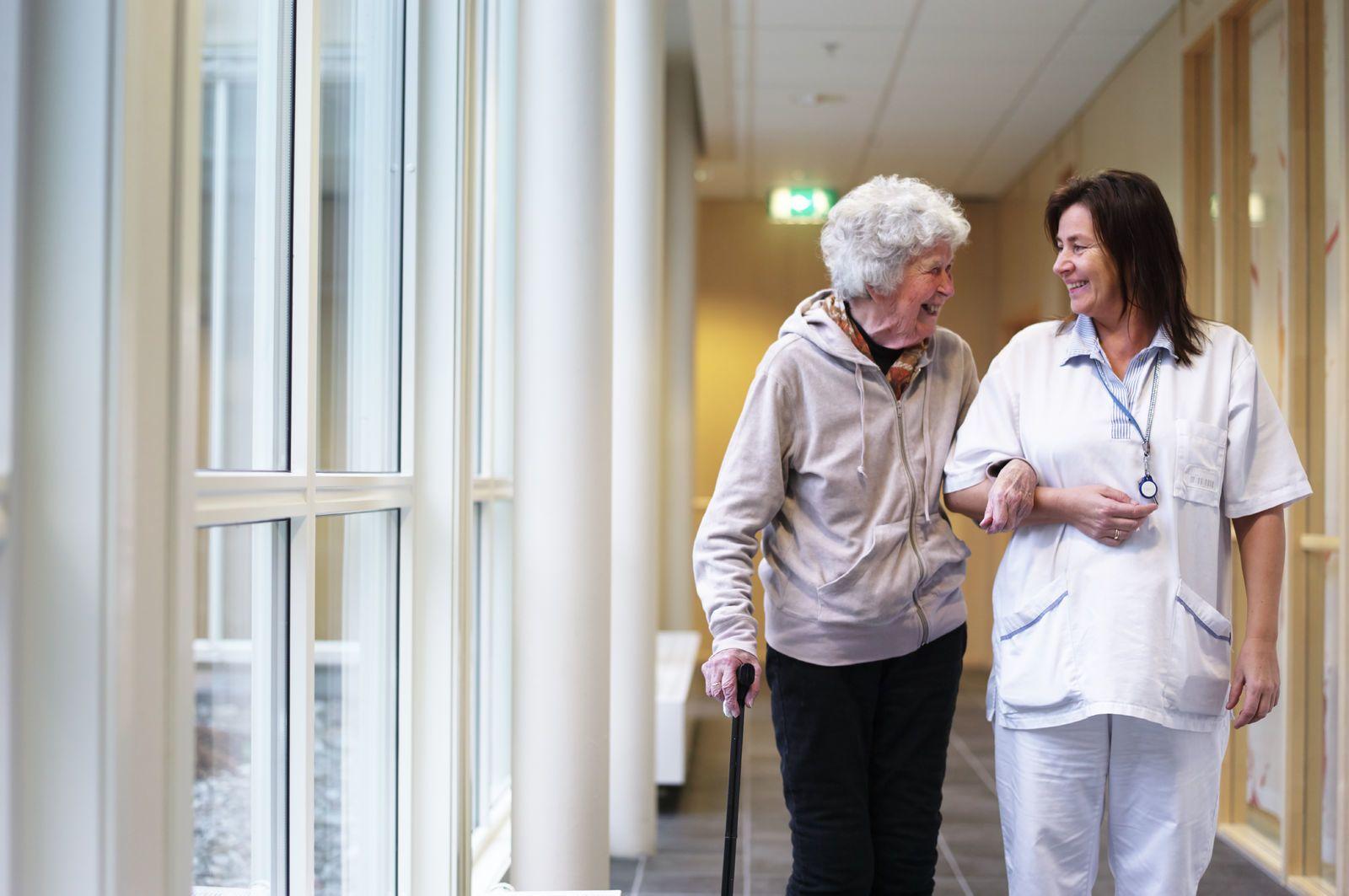 En helsearbeider geleider en eldre dame gjennom gangene i et helsebygg. Foto: Øivind Haug