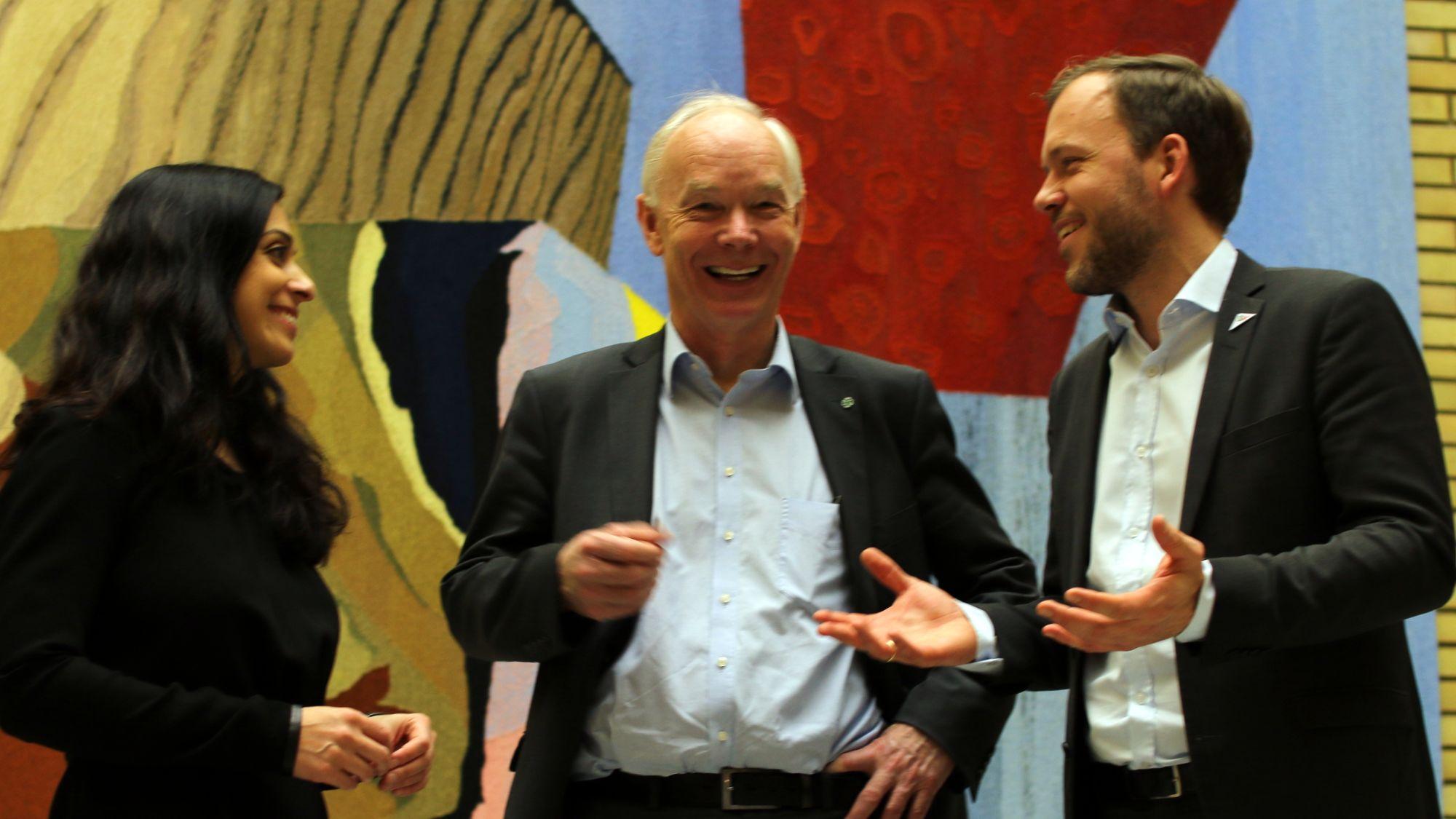 Hadia Tajik, Per Olav Lundteigen (Sp) og Audun Lysbakken (SV) smilende i Stortingets vandrehall