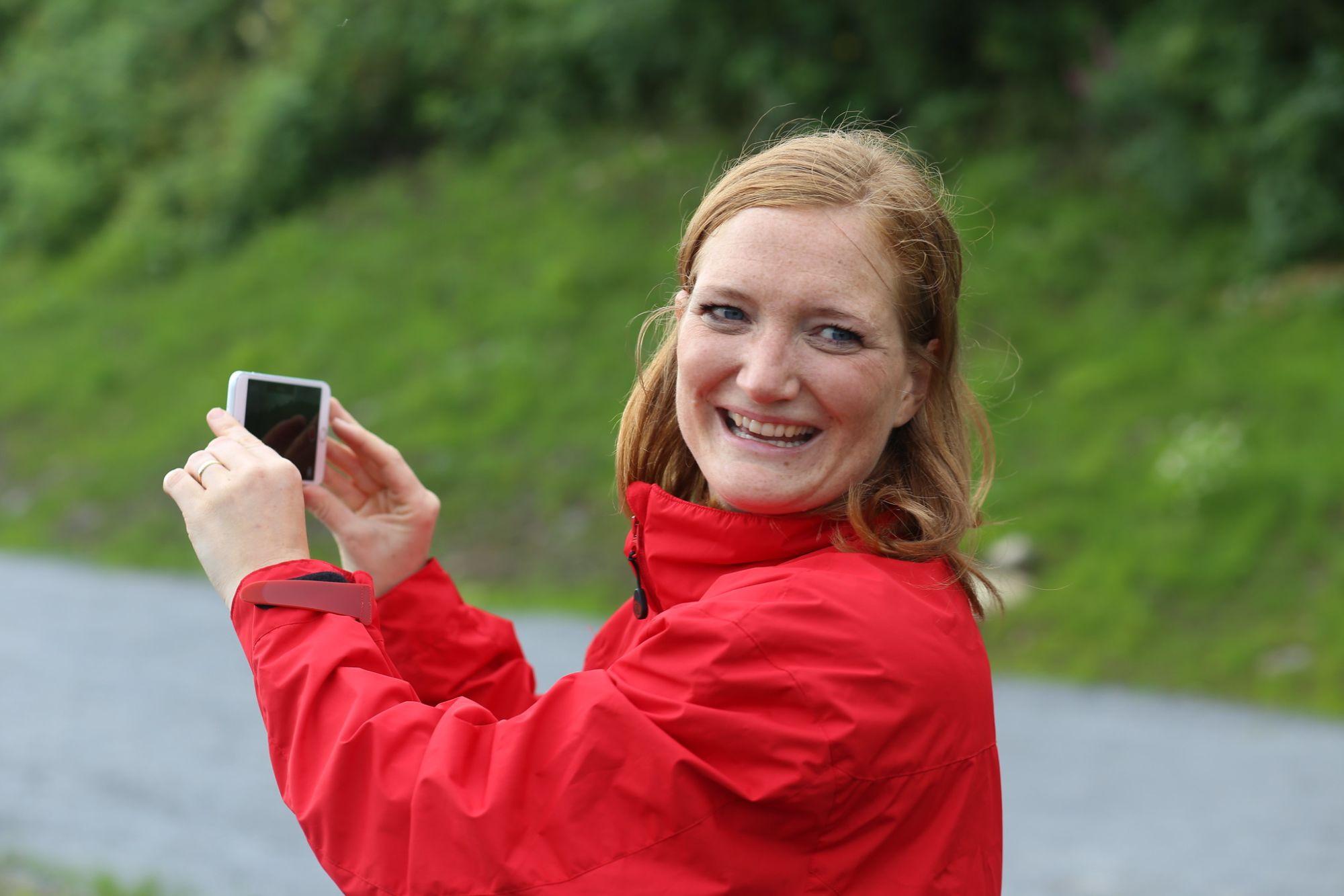 Bodøs ordførerkandidat Ida Pinnerød står utendørs smilende i rød jakke. Hun holder en mobiltelefon i hendene. Bak henne er grønt gress og noen busker.
