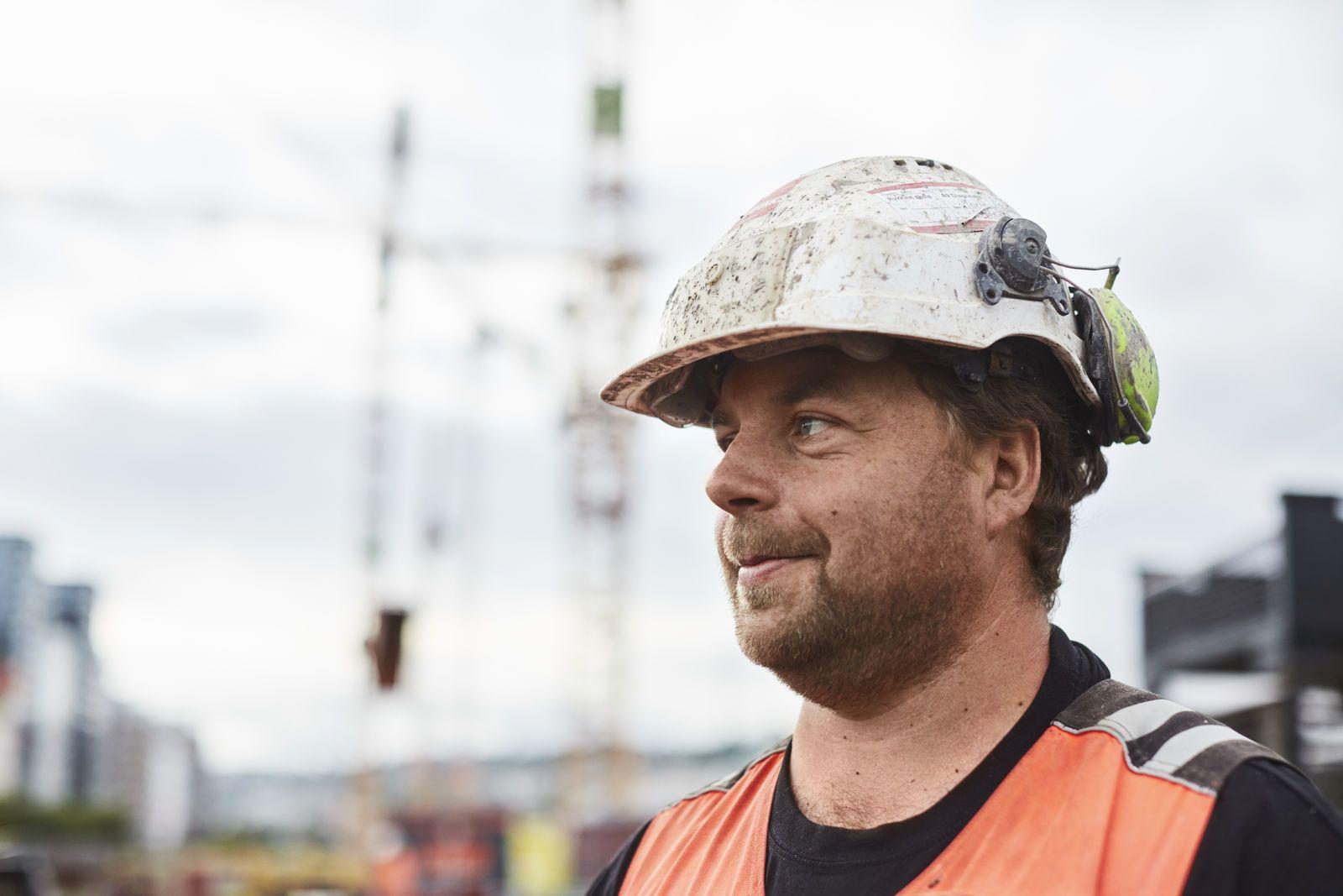 En anleggsarbeider står sidevendt mot kamera, i bakgrunnen ser vi heisekraner og hus. Foto: Øivind Haug