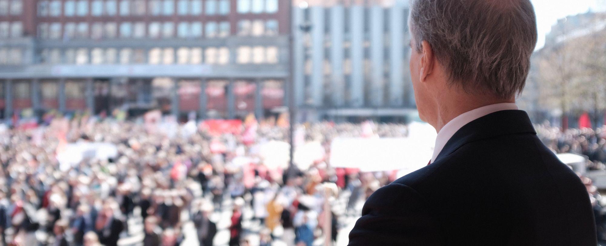 Jonas Gahr Støre bakfra med utsikt over Youngstorget mens han holder 1. mai-tale. Mange mennesker står nede på torget.