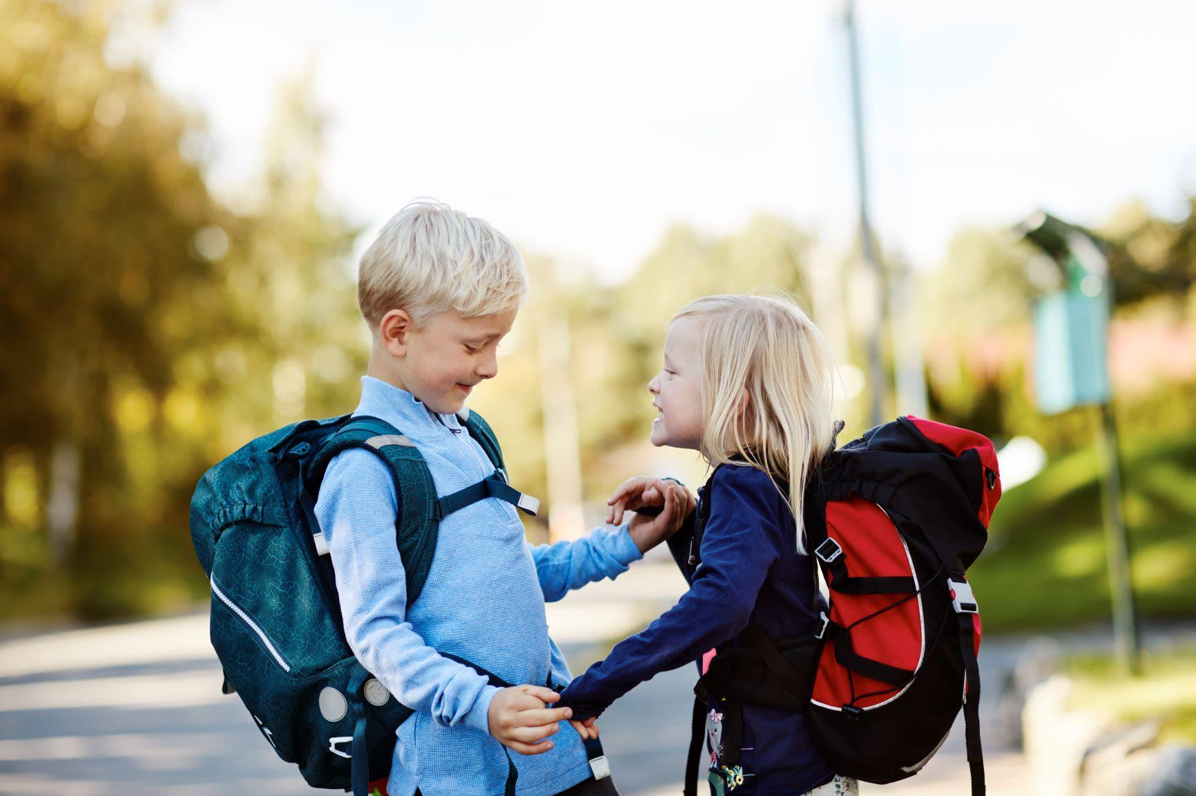Liten gutt og liten jente med skolesekker stående smilende mot hverandre
