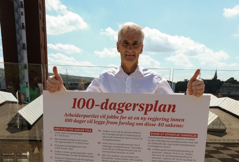 Jonas Gahr Støre med Arbeiderpartiets 100-dagersplan plakat.