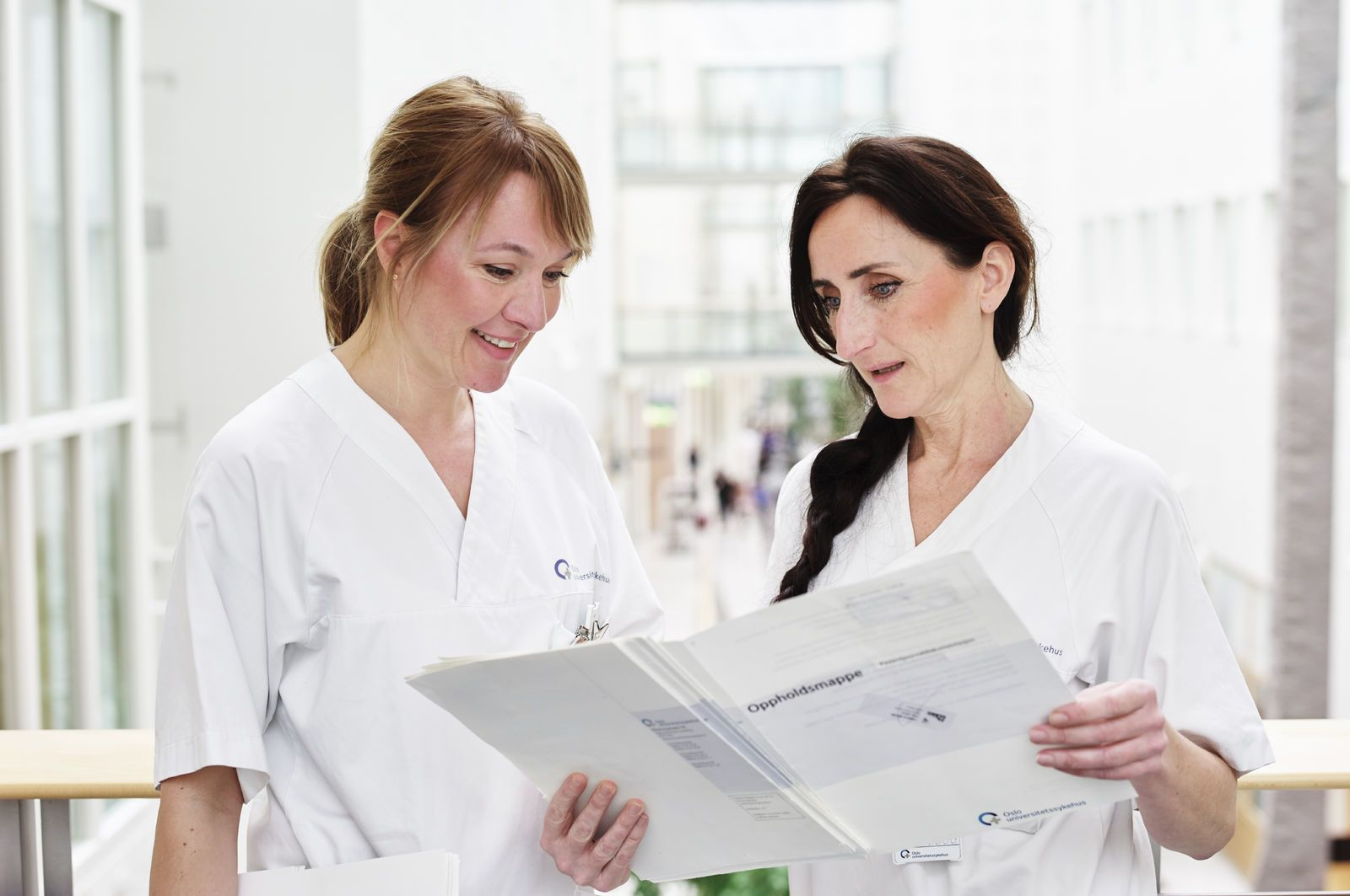 To helsearbeidere står samlet over, og diskuterer, sykehusjournaler. Foto: Øivind Haug