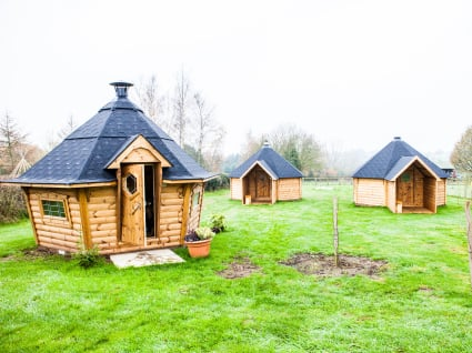 Three camping cabins on a grassy field.